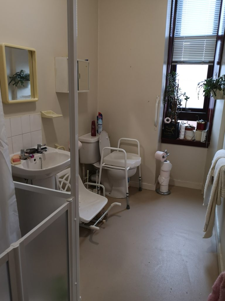 Bathroom after the adaptation for disability access with walk in shower and wetroom safety flooring